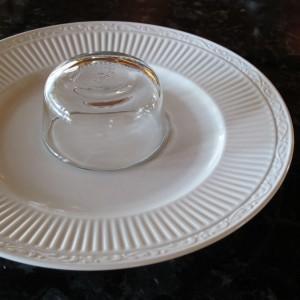 Um eine Couronne-Form zu machen, eine kleine Schale auf einem Teller befestigen.